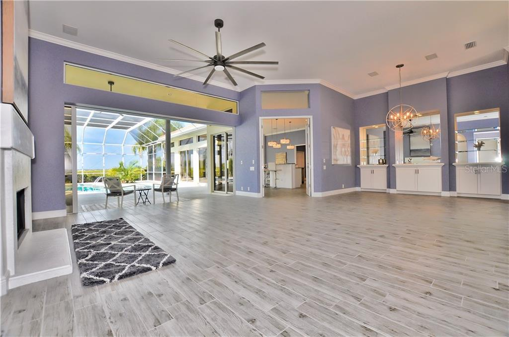 The large sliders in the formal living room with a fireplace opens into the newly remodeled kitchen with a wet bar that is mirrored. - Single Family Home for sale at 3121 Rivershore Ln, Port Charlotte, FL 33953 - MLS Number is D5917816