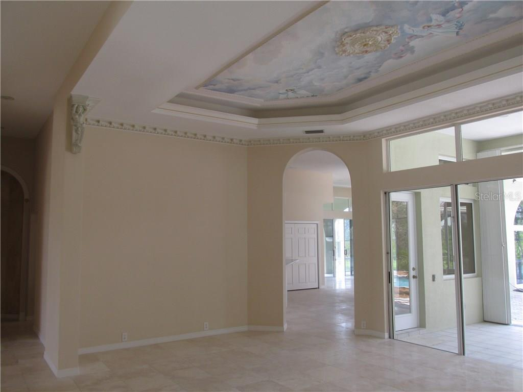 This is a view of the living room looking toward the kitchen and family room area.  Note the fresco ceiling and extensive plaster trim - Single Family Home for sale at 3001 Rivershore Ln, Port Charlotte, FL 33953 - MLS Number is D5917929