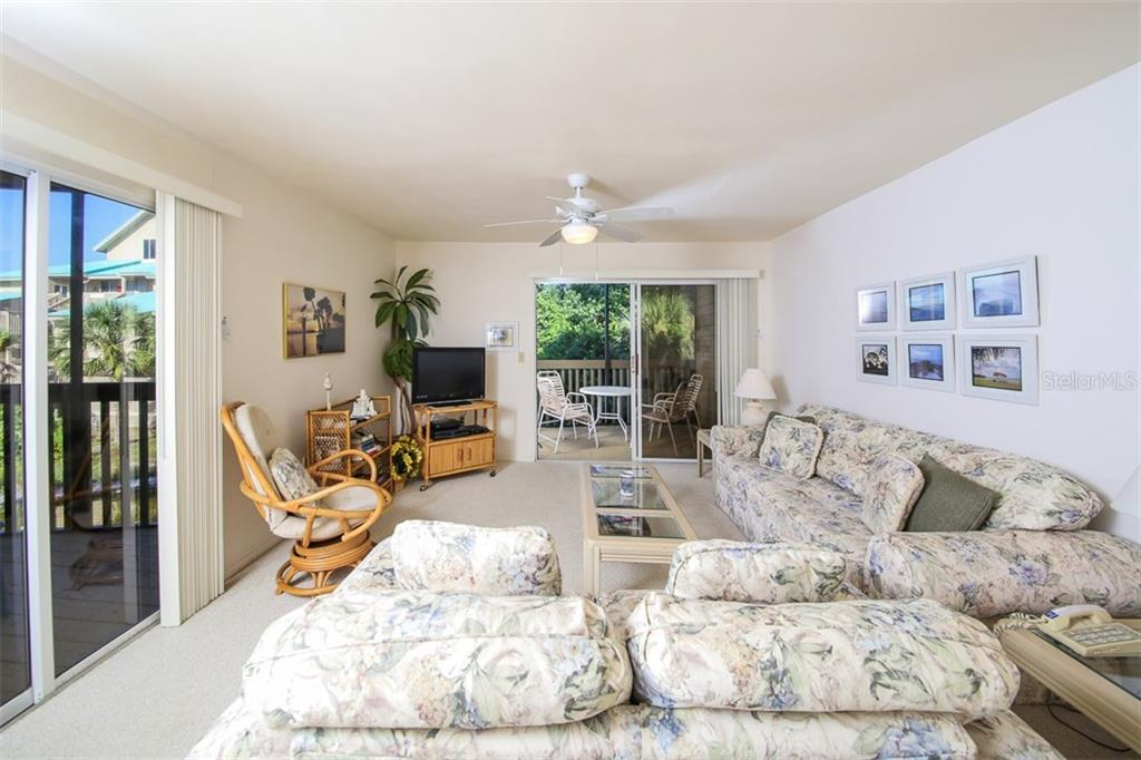 Living room with sliders to 2 screened porches - Condo for sale at 9200 Little Gasparilla Is #203, Placida, FL 33946 - MLS Number is D5920072