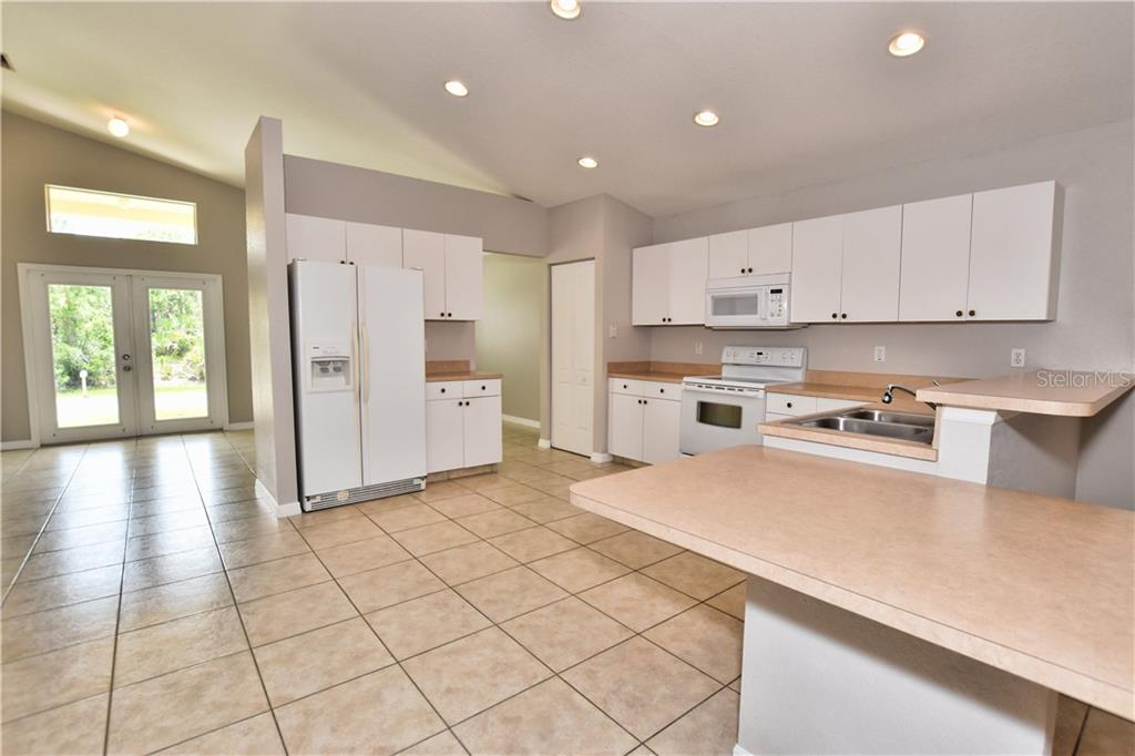 Kitchen with breakfast bar and eat in space, dining area to the right.  Kitchen, dining opens to great room and flows to the Lanai. - Single Family Home for sale at 4414 Callaway St, Port Charlotte, FL 33981 - MLS Number is D6100799