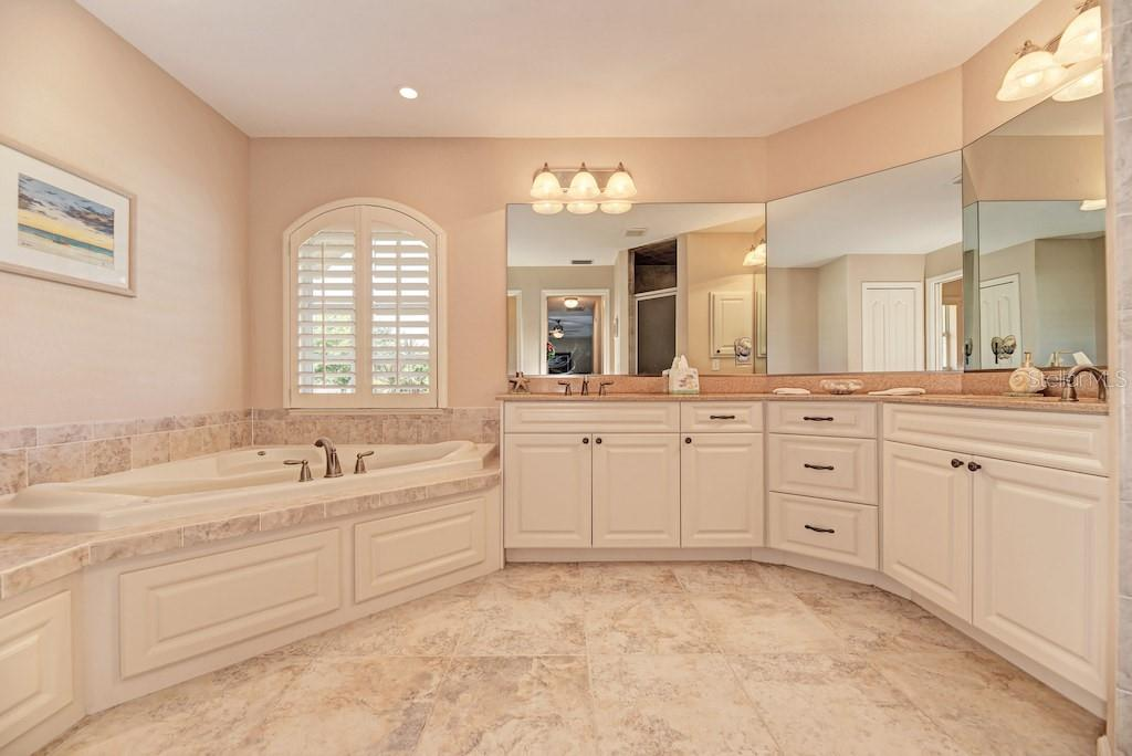 Gorgeous master bath with Jacuzzi tub, double vanity, plantation shutters, separate shower stall, and private water closet. - Single Family Home for sale at 7256 Holsum St, Englewood, FL 34224 - MLS Number is D6101787