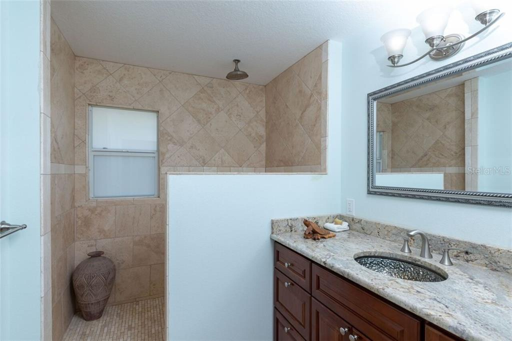 A roman style shower with travertine and a rain shower head will get every morning off to a perfect start. The glass bowl in the sink is just another of the little extras to appreciate in this tastfully designed living space. - Single Family Home for sale at 7339 Hawkins Rd, Sarasota, FL 34241 - MLS Number is D6102762