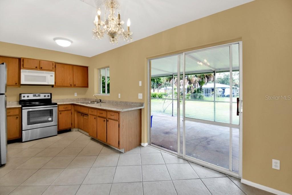 Kitchen, slider to lanai - Single Family Home for sale at 20233 Peachland Blvd, Port Charlotte, FL 33954 - MLS Number is D6107765