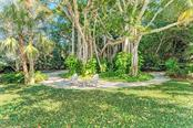 Reminisce about days gone by in the shade of one of the massive banyan trees on the property. - Single Family Home for sale at 7400 Manasota Key Rd, Englewood, FL 34223 - MLS Number is D6104362