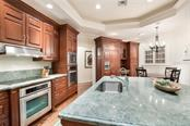 Kitchen accents include custom cherry cabinetry, granite counters, lighted tray ceiling - Single Family Home for sale at 1600 E Railroad Ave, Boca Grande, FL 33921 - MLS Number is D6108744