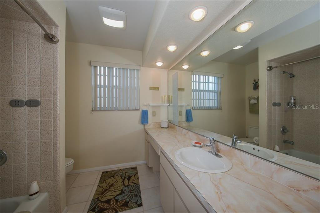 Hall bath 2 with expansive vanity & tiled tub - Single Family Home for sale at 2332 Mauritania Rd, Punta Gorda, FL 33983 - MLS Number is C7234250