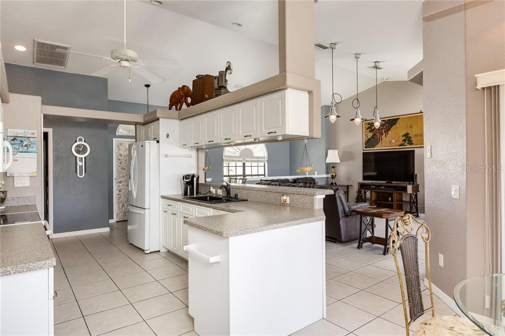 Kitchen w/cathedral ceiling and access to interior laundry room - Single Family Home for sale at 515 Royal Poinciana Cir, Punta Gorda, FL 33955 - MLS Number is C7244338