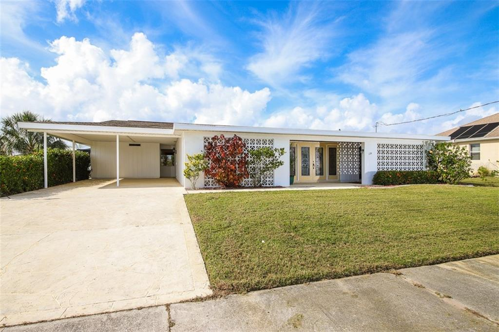Very spacious carport with cement stone accent driveway has large storage room beyond. - Single Family Home for sale at 126 Bangsberg Rd Se, Port Charlotte, FL 33952 - MLS Number is C7409866