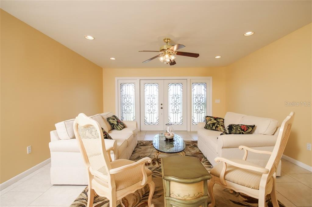 Decorative front entry doors expand into a welcoming sitting area in the Living Room. - Single Family Home for sale at 126 Bangsberg Rd Se, Port Charlotte, FL 33952 - MLS Number is C7409866