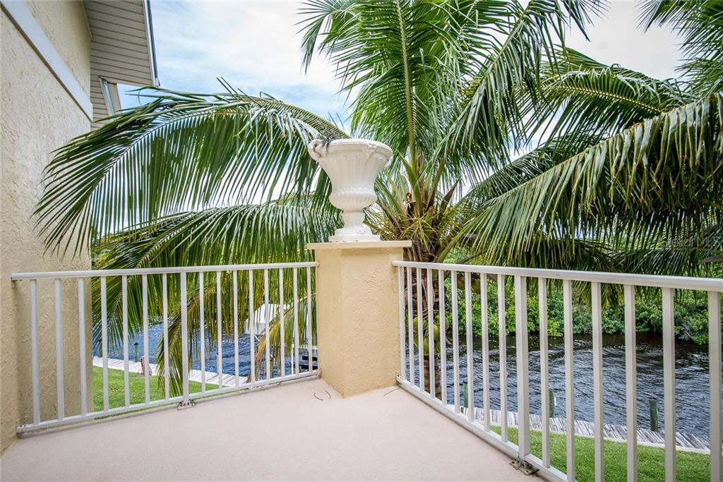 This private balcony overlooks the canal, dock and preserved lands and is accessible from two of the guest ensuite bedrooms on the second level. - Condo for sale at 4410 Warren Ave #511, Port Charlotte, FL 33953 - MLS Number is C7432222