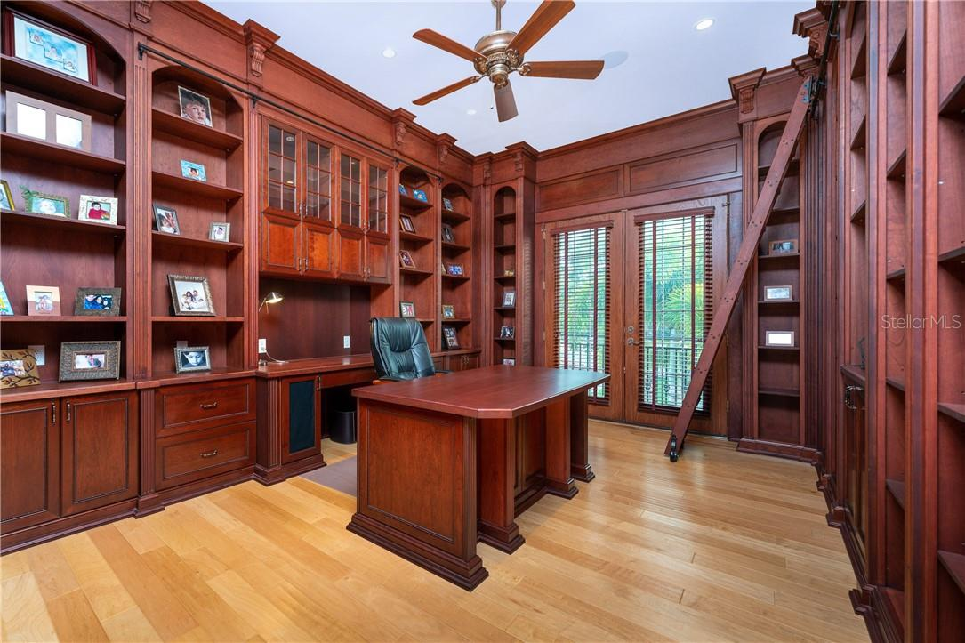 The Cherry and Maple wood-clad executive office is superb and includes floor-to-ceiling bookcases, a rolling library ladder, and French doors leading to an outside balcony - Single Family Home for sale at 7440 Riverside Dr, Punta Gorda, FL 33982 - MLS Number is C7436263