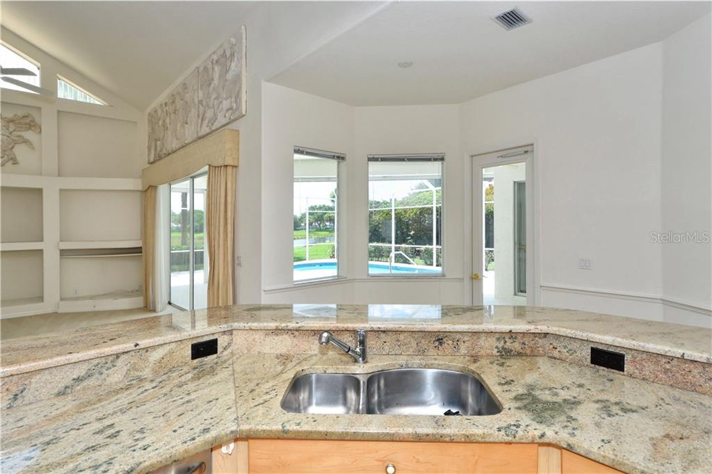 The kitchen affords gorgeous views of the family room, lanai, heated pool and distant water.  A breakfast bar sits atop this entire island with plenty of space for seating. - Single Family Home for sale at 8753 Merion Ave, Sarasota, FL 34238 - MLS Number is A4165409