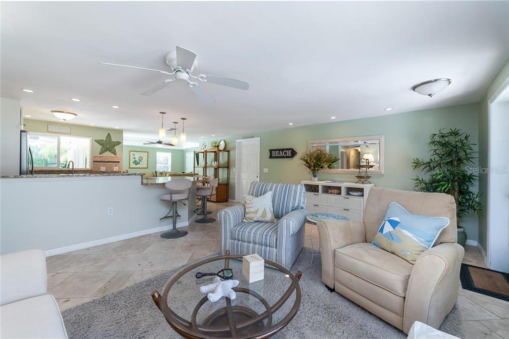 The living room opens to the kitchen and great room beyond. - Single Family Home for sale at 413 Bay Palms Dr, Holmes Beach, FL 34217 - MLS Number is A4184679