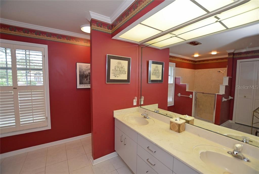Master ensuite bath with dual sinks, crown molding, and tiled shower. - Single Family Home for sale at 1157 Wyeth Dr, Nokomis, FL 34275 - MLS Number is A4185839