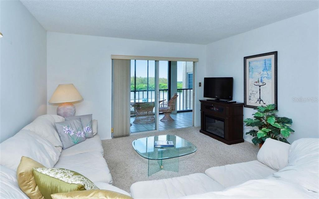 Living room with sliders to balcony - Condo for sale at 9397 Midnight Pass Rd #403, Sarasota, FL 34242 - MLS Number is A4185842