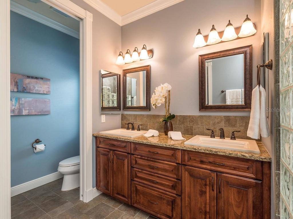 Dual sinks with gorgeous granite and wood cabinetry, private restroom with pocket door and linen closet. - Single Family Home for sale at 1884 Grove St, Sarasota, FL 34239 - MLS Number is A4189365