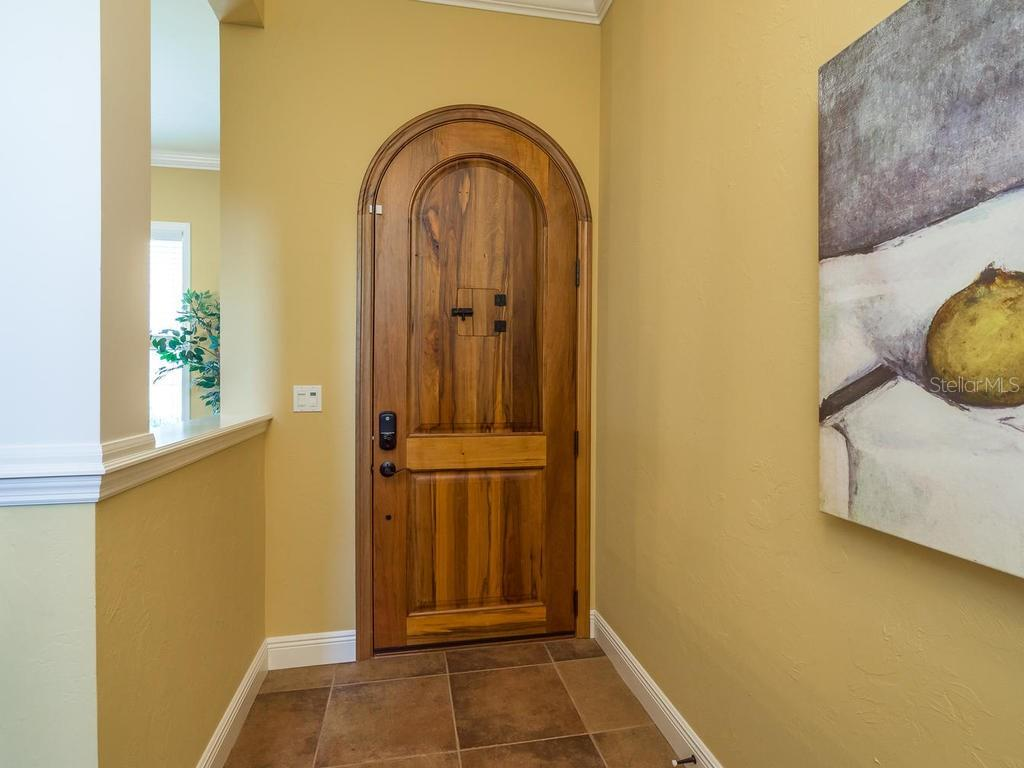 Beautiful 8-ft arched wooden door with viewing door. - Single Family Home for sale at 1884 Grove St, Sarasota, FL 34239 - MLS Number is A4189365