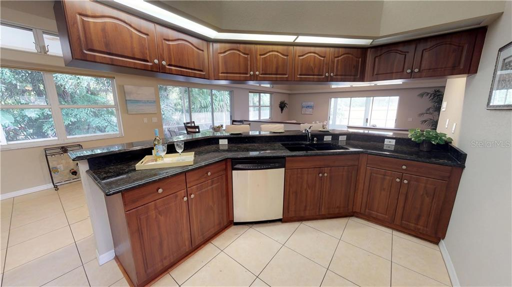 The kitchen from the other side with it's long wrap around bar, looking out over the beautiful gardens beyond - Single Family Home for sale at 9122 16th Avenue Cir Nw, Bradenton, FL 34209 - MLS Number is A4189396