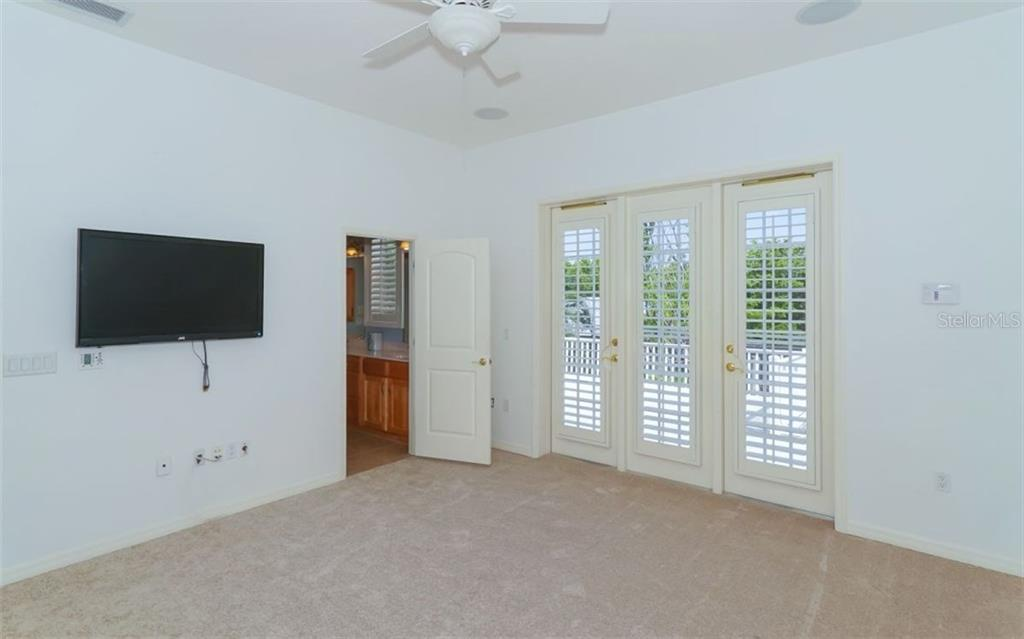 One of four bedrooms, all of which are upstairs and open to a balcony through French doors with plantation shutters.   There is a Jack and Jill bath between two of the bedrooms. - Single Family Home for sale at 9818 9th Ave Nw, Bradenton, FL 34209 - MLS Number is A4194125