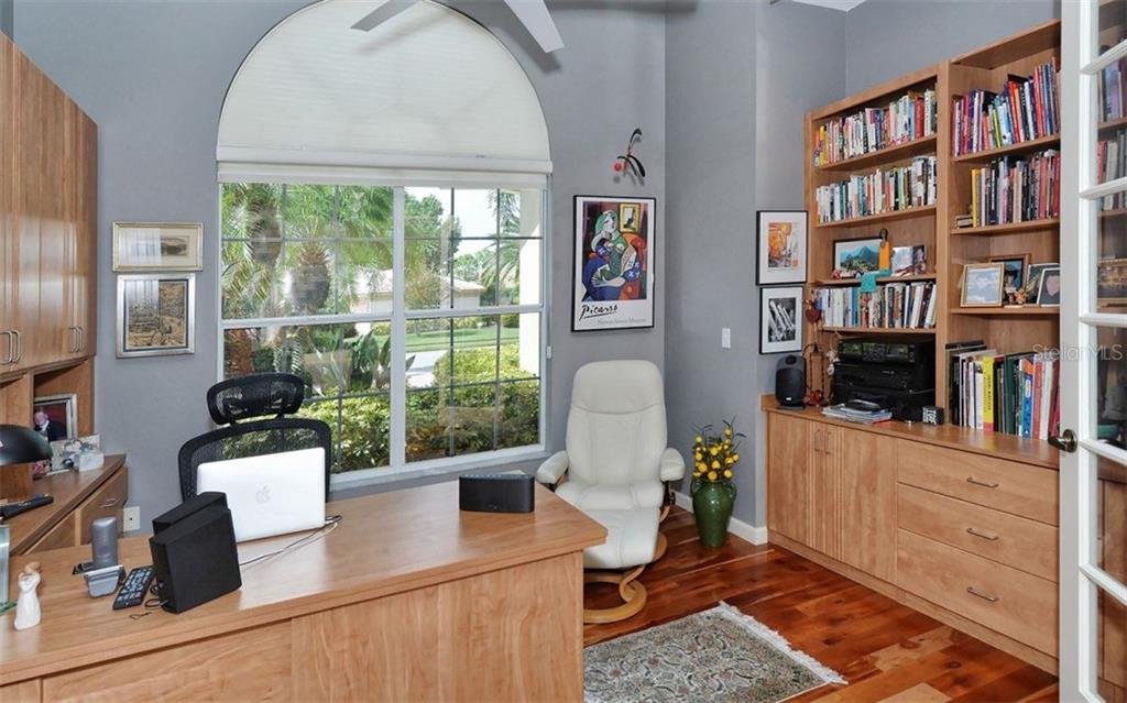 The bright and light den/office has built-in bookcases, cabinets and desk, French doors, double windows, crown molding and 12' ceiling. - Single Family Home for sale at 8747 Grey Oaks Ave, Sarasota, FL 34238 - MLS Number is A4195019