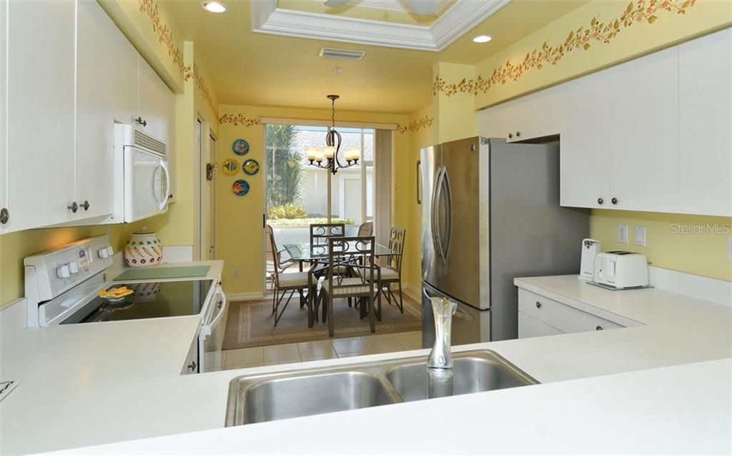 Kitchen has lots of counter space and cabinets and a dinette area with sliders to front lanai. - Condo for sale at 9570 High Gate Dr #1712, Sarasota, FL 34238 - MLS Number is A4196327