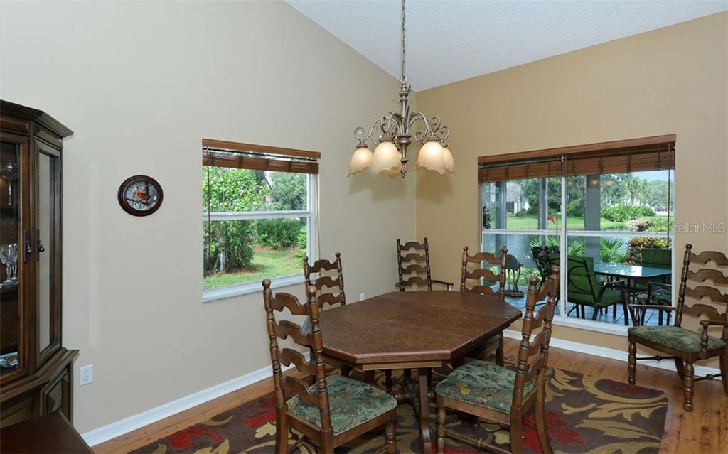 Dining room is bathed with windows. - Single Family Home for sale at 9571 Knightsbridge Cir, Sarasota, FL 34238 - MLS Number is A4197972