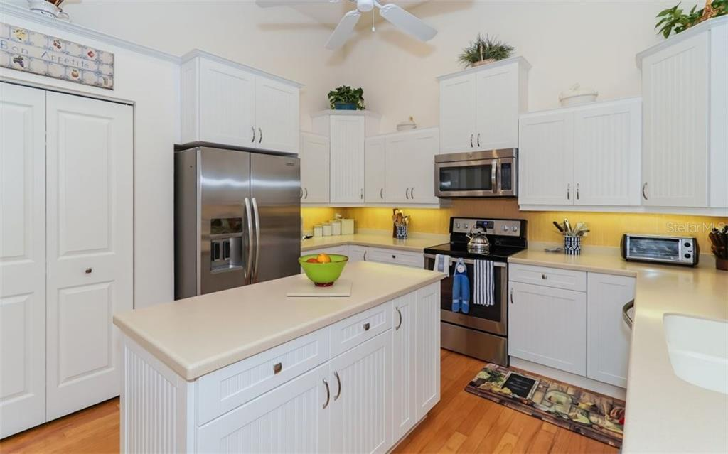 Kitchen with Corian Counters, White Cabinets, Under Counter Lighting and Pantry - Single Family Home for sale at 460 Otter Creek Dr, Venice, FL 34292 - MLS Number is A4205372