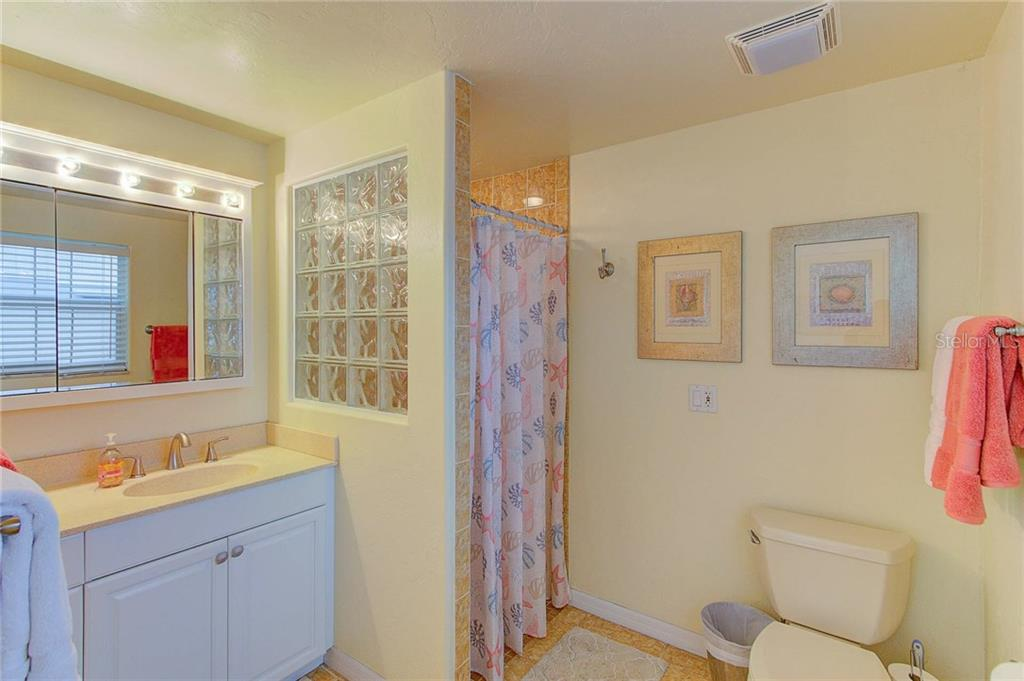 The master bath with walk-in shower is updated with new hardware and refinished cabinetry. - Single Family Home for sale at 501 70th St, Holmes Beach, FL 34217 - MLS Number is A4205799