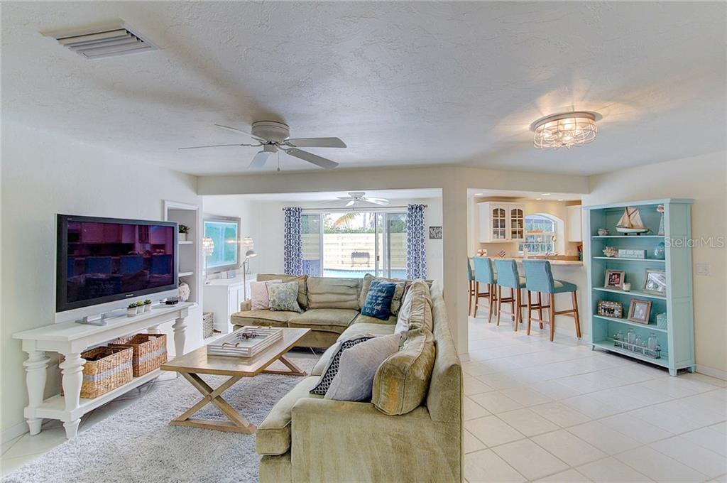 Living area and breakfast bar with a wall of sliders leading to the pool area. - Single Family Home for sale at 501 70th St, Holmes Beach, FL 34217 - MLS Number is A4205799
