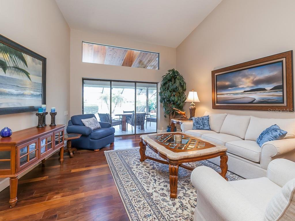 Living Room with sliding doors and a large transom window to the pool and spa areaa - Single Family Home for sale at 3959 Prairie Dunes Dr, Sarasota, FL 34238 - MLS Number is A4205907