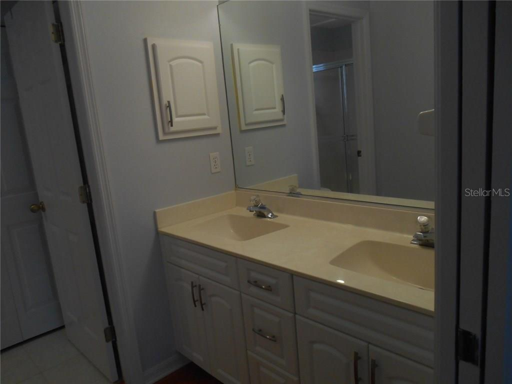 The master bath boasts dual sinks, newly refaced vanities, with a linen closet and shower to the left.  The walk-in closet is to the left opposite the vanity.  Note the space-saving pocket door! - Condo for sale at 815 Montrose Dr #202, Venice, FL 34293 - MLS Number is A4206556