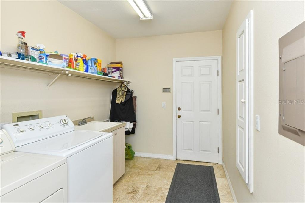 Nice size utility room with door to garage. Note fold out ironing board on the right wall. - Single Family Home for sale at 7536 Weeping Willow Dr, Sarasota, FL 34241 - MLS Number is A4210209