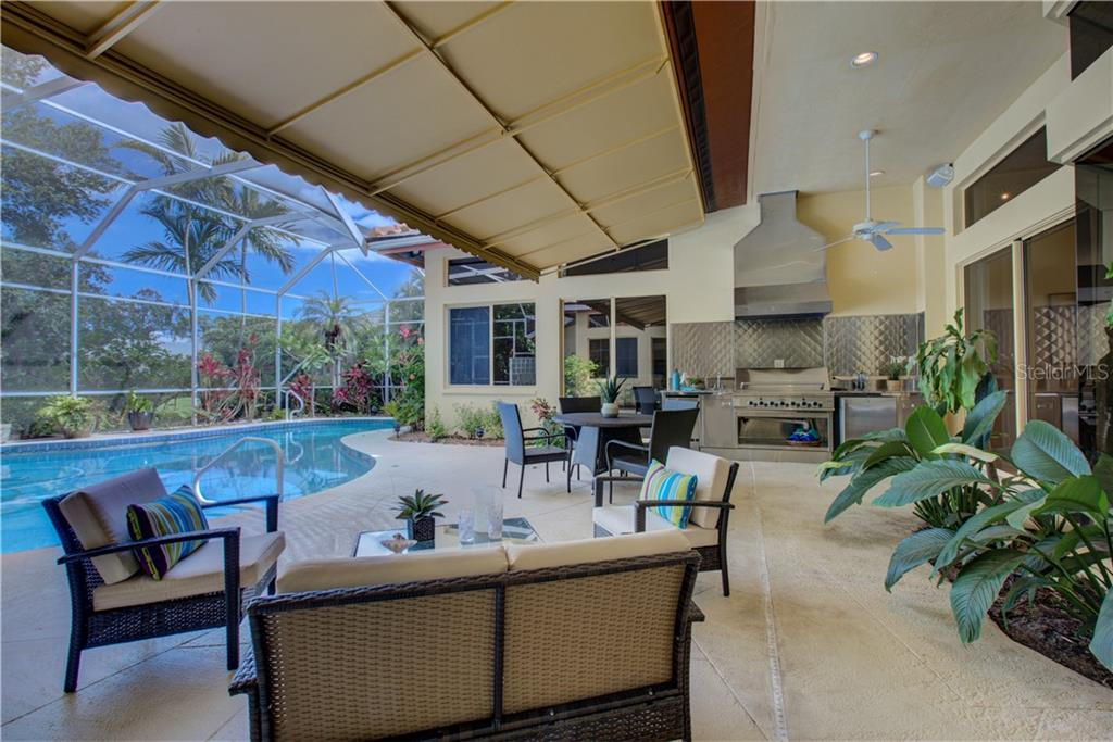 Spacious covered outdoor patio with fully fitted kitchen to include a large 8 burner gas grill, exhaust hood, ice maker, refrigerator and sink. - Single Family Home for sale at 3896 Boca Pointe Dr, Sarasota, FL 34238 - MLS Number is A4213831