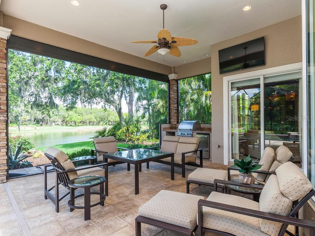 Sliders from the den/office to out to the large veranda with the most unbelievable view and an outdoor kitchen. - Single Family Home for sale at 12312 Newcastle Pl, Lakewood Ranch, FL 34202 - MLS Number is A4403090