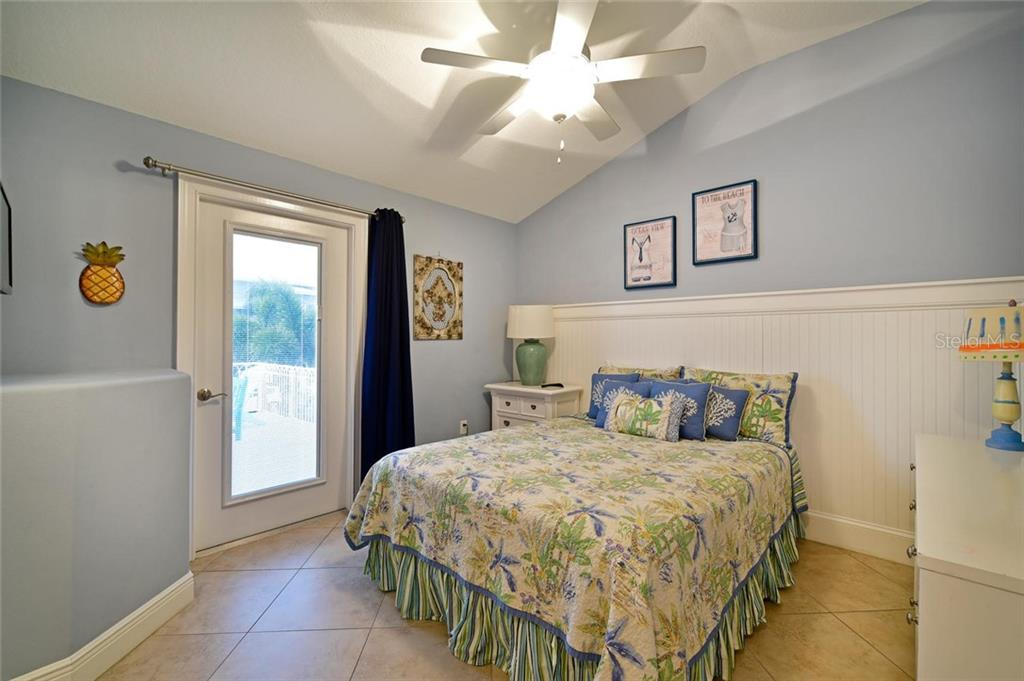 This large upstairs bedroom has its own bath and a door to the second story deck, just in case you wake up in the middle of the night and need to see the stars and hear the waves breaking a short distance away. - Single Family Home for sale at 113 36th St, Holmes Beach, FL 34217 - MLS Number is A4407267