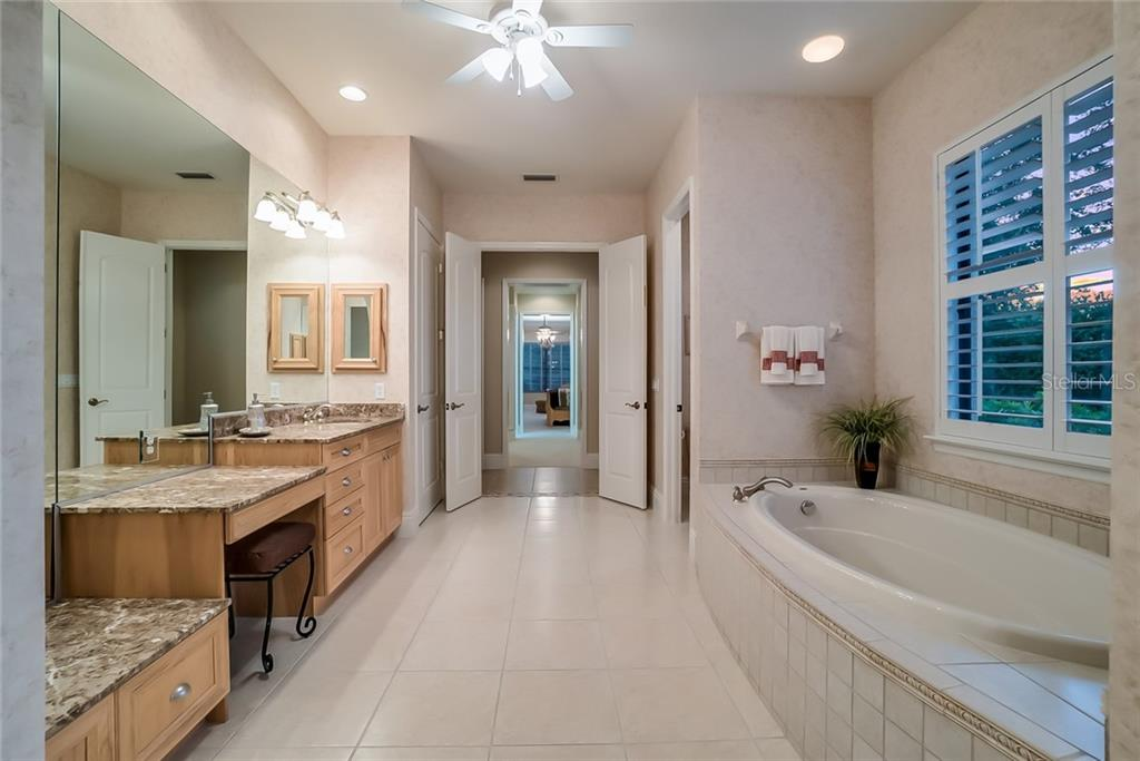 Master Bathroom: to the left - triple counters with sit-down vanity, sink, granite counters and plenty of storage. To the right is a garden tub and private door to the water closet. - Single Family Home for sale at 13223 Palmers Creek Ter, Lakewood Ranch, FL 34202 - MLS Number is A4408290