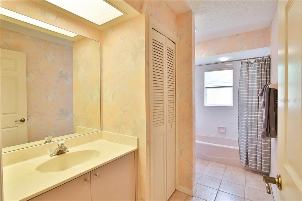 Second Full Bathroom shared by Bedrooms 2 & 3. - Villa for sale at 7686 Calle Facil, Sarasota, FL 34238 - MLS Number is A4413755