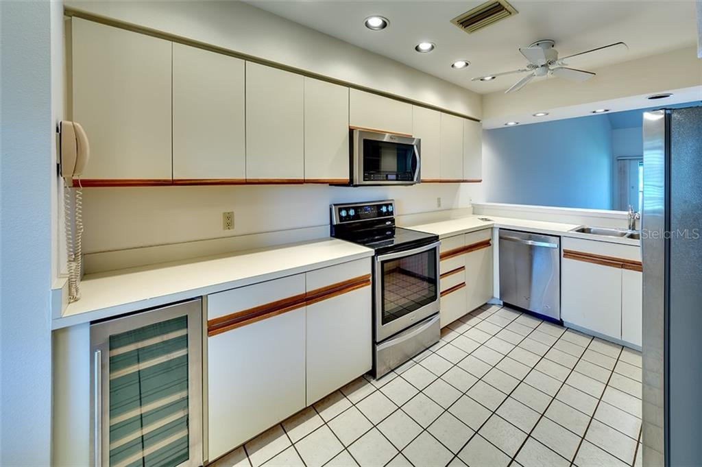 Kitchen opens to dining room/living room area with Bay views. Newer appliances and wine refrigerator. - Condo for sale at 3920 Mariners Way #323a, Cortez, FL 34215 - MLS Number is A4416115