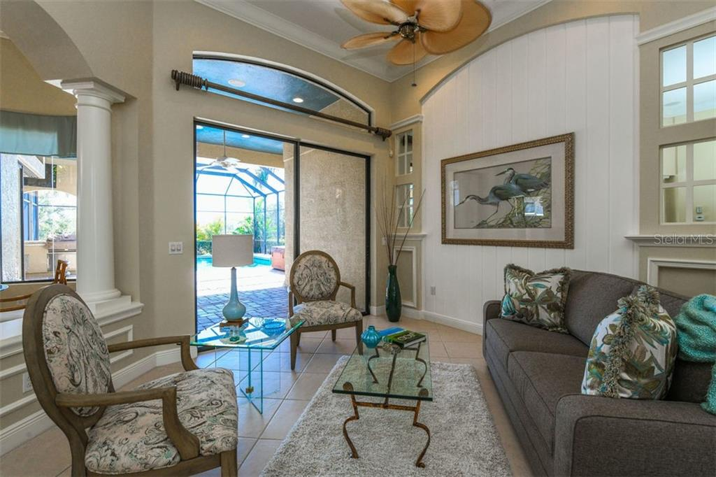 Cozy Living Room with Gorgeous Pool & Tropical Landscape Views - Single Family Home for sale at 7060 Whitemarsh Cir, Lakewood Ranch, FL 34202 - MLS Number is A4417363