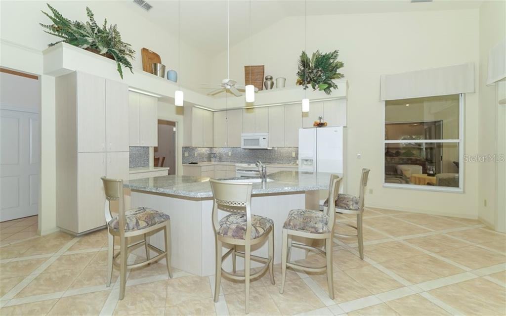 Stunning kitchen with stone counters, large island & breakfast bar, pendant lighting. - Single Family Home for sale at 6125 Varedo Ct, Sarasota, FL 34243 - MLS Number is A4420656