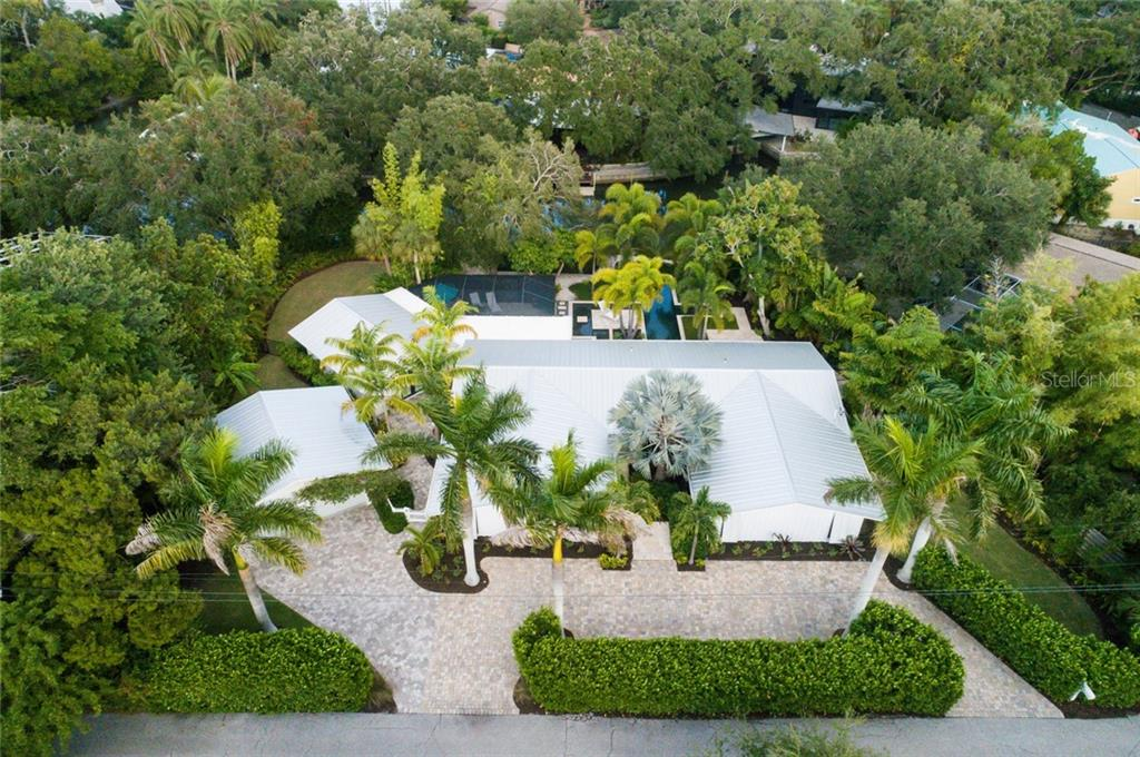 Circular driveway, free standing garage behind tall privacy hedge - Single Family Home for sale at 6957 Belgrave Dr, Sarasota, FL 34242 - MLS Number is A4423362