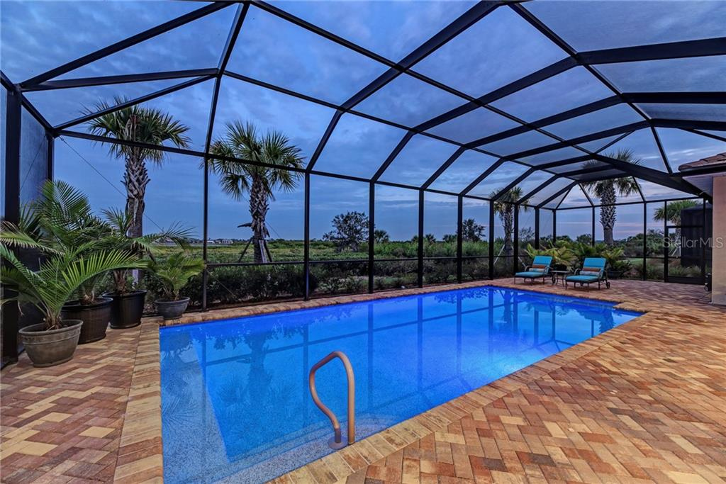 Swimming pool with pool lighting in evening - Single Family Home for sale at 5712 Tidewater Preserve Blvd, Bradenton, FL 34208 - MLS Number is A4424693