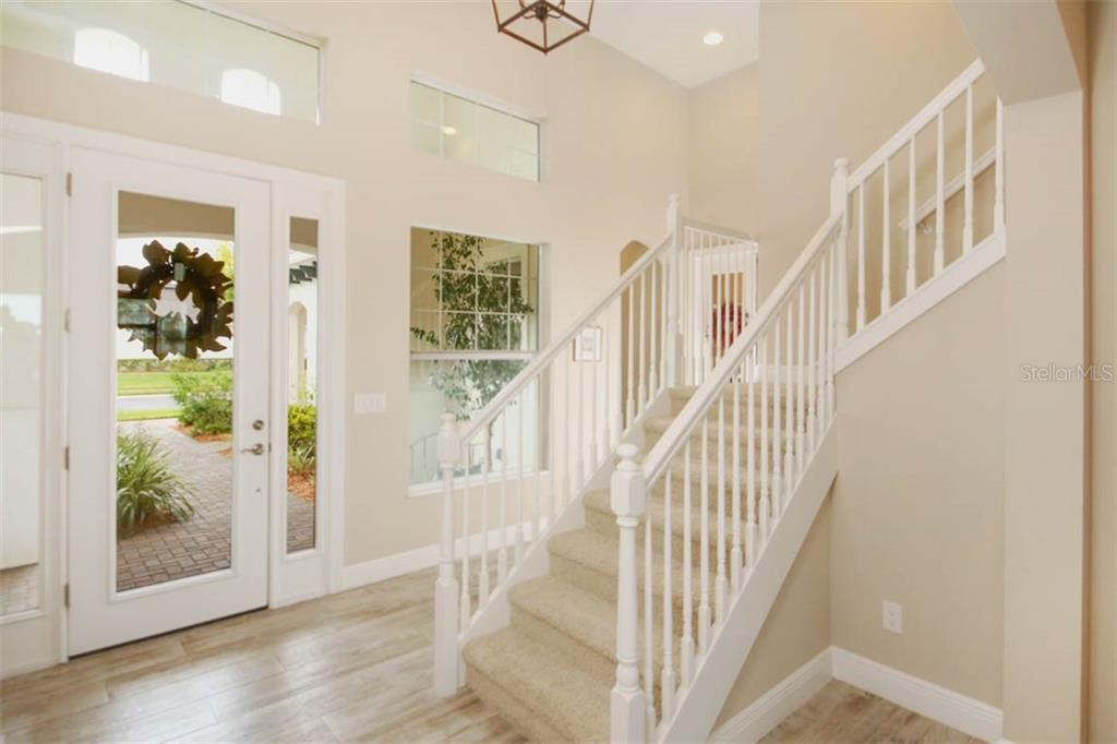 Staircase leads to a large bonus/media room, half bath, 3 closets, and fantastic screened balcony - Single Family Home for sale at 5504 Tidewater Preserve Blvd, Bradenton, FL 34208 - MLS Number is A4429479