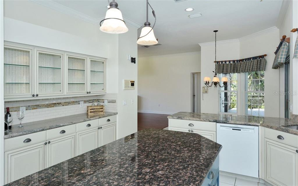 Beautifully updated kitchen offers lots of solid wood cabinetry and granite countertops, a chefs dream! - Single Family Home for sale at 1636 Liscourt Dr, Venice, FL 34292 - MLS Number is A4429524