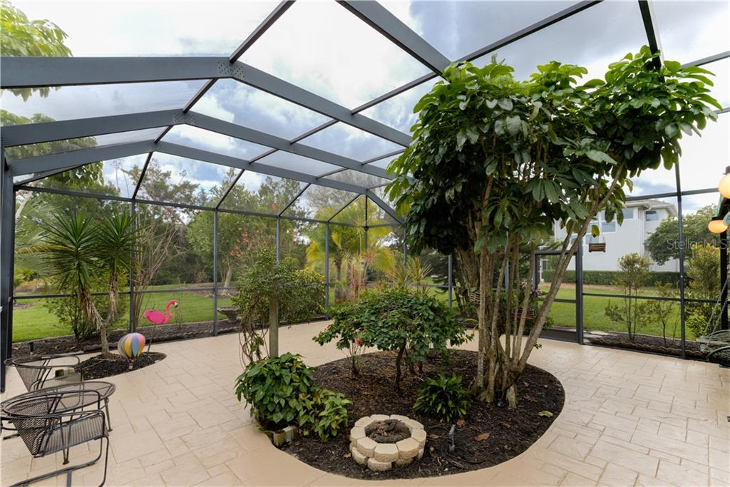 Gorgeous huge screened patio with gas fire pit and flowering plants - Single Family Home for sale at 6321 W Glen Abbey Ln E, Bradenton, FL 34202 - MLS Number is A4429610
