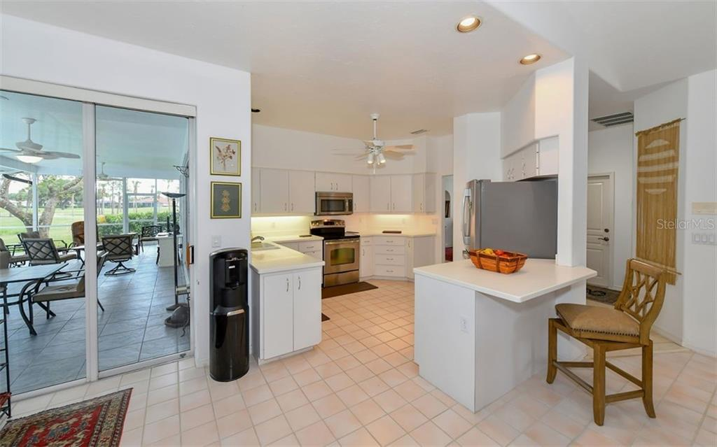 kitchen, breakfast bar and sliders to lanai, pool and spa - Single Family Home for sale at 5401 Downham Meadows, Sarasota, FL 34235 - MLS Number is A4436577