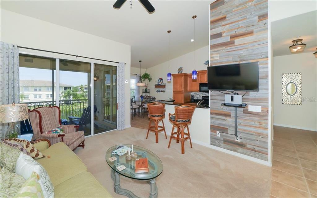 Living room with feature newly installed feature wall adjacent to kitchen and lanai. - Condo for sale at 200 San Lino Cir #233, Venice, FL 34292 - MLS Number is A4440138