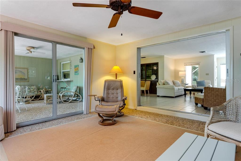 The kitchen window overlooks the screened in lanai out to the water. Sliders lead from the dining room and the Florida room. - Single Family Home for sale at 701 Norton St, Longboat Key, FL 34228 - MLS Number is A4440596