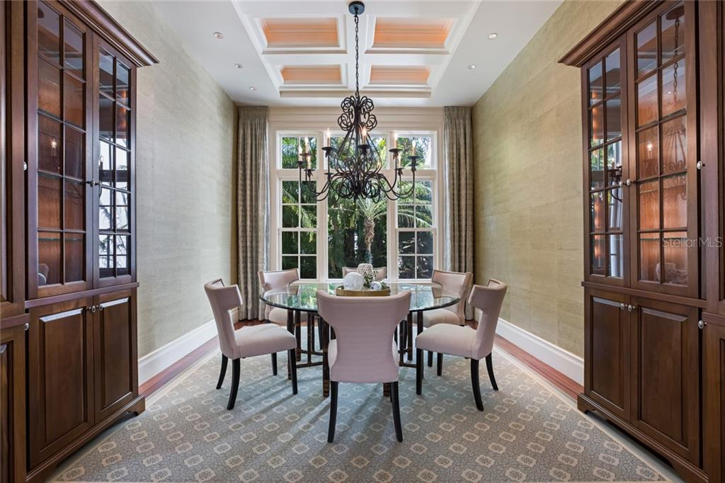 Formal dining room with coffered ceiling and custom built-ins. - Single Family Home for sale at 1522 N Lake Shore Dr, Sarasota, FL 34231 - MLS Number is A4442286