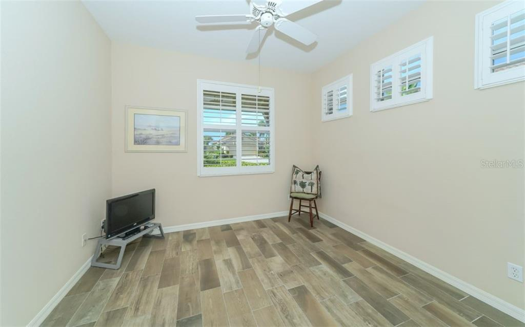 Second bedroom with wood look tile floors and plantation shutters. - Single Family Home for sale at 114 Padova Way #52, North Venice, FL 34275 - MLS Number is A4442496